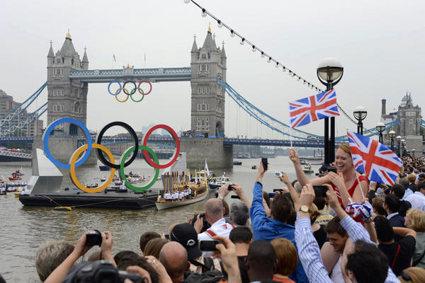The Olympic torch is delivered by row boat to the royal barge, Gloriana, on the River Thames, near Tower Bridge in London ahead of the opening ceremony on Friday.