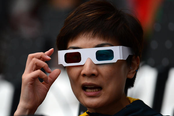 A fan wearing 3-D glasses watches the ceremony.