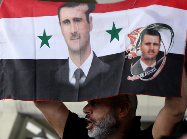 A Syrian man holds a national flag bearing pictures of President Bashar Assad during a pro-regime protest to condemn a deadly attack in the central Midan district of Damascus on April 27.