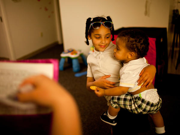 Shyanne (left) holds 1-year-old Makai, as Stepp checks to see if all of Shyanne's homework has been completed.