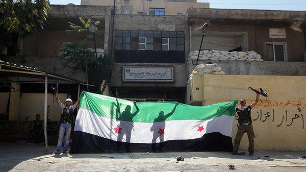 A picture released by the Syrian opposition's Shaam News Network purportedly shows Syrian rebels celebrating after taking over a police station in the Ansari district of Aleppo on Friday.