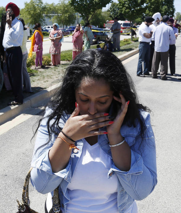 Anxiously waiting for word: Family and friends of those who were inside the Sikh temple gathered nearby as they waited for news about their loved ones.