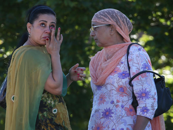A woman wipes away a tear in front of the Sikh Temple of Wisconsin on Sunday in Oak Creek.
