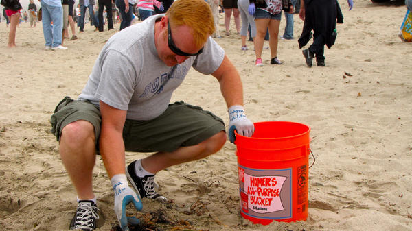A volunteer picks up trash at a Nothin' But Sand beach cleanup.