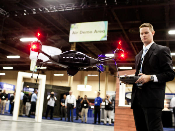 """Brian Bills, a flight operations analyst for Lockheed Martin, demonstrates the Procerus VTOL (vertical takeoff and landing) Flight System — a surveillance drone for commercial, civil and military customers — at the Association of Unmanned Vehicle Systems International conference in Las Vegas. (<a href=""""http://www.youtube.com/watch?v=_GttUgRfWnE"""">Watch a demo video</a>.)"""