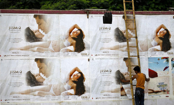 "A man pastes the posters of Bollywood film ""Jism 2"" outside a cinema hall in Bangalore, India."