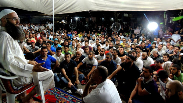 Sheik Ahmad Assir speaks to supporters at a tent encampment set up in protest against Hezbollah in Sidon, Lebanon. He accuses the Islamist militant group of using resistance against Israel as a smokescreen for another aim: advancing Iranian regional hegemony.