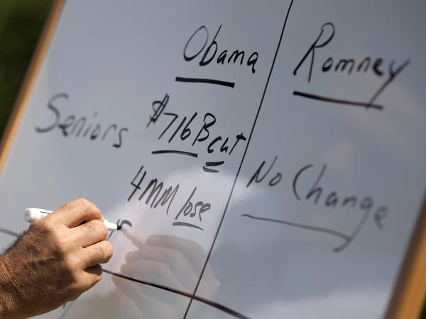 Mitt Romney writes on a whiteboard as he talks about Medicare during a news conference on Aug. 16 in Greer, S.C.