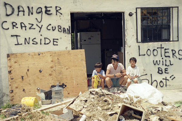 Orlando Somante sits with his sons Orlando (left) and Jonathan amid the rubble of their home in Cutler Ridge.