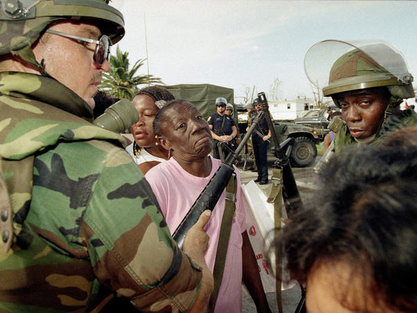 Florida National Guardsmen keep people in line at a food distribution center in Florida City, Fla., on Aug. 27, 1992. Many residents of the Dade County farming community lost their homes to Hurricane Andrew.