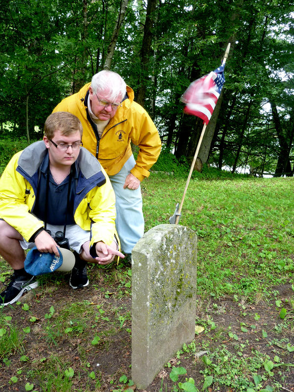 Jack Grobe (left) and Ken Deedy inspect a gravestone in one of Grindstone Island's unofficial cemeteries. Although he's only 19, Grobe says he'd like to be buried on the island someday.
