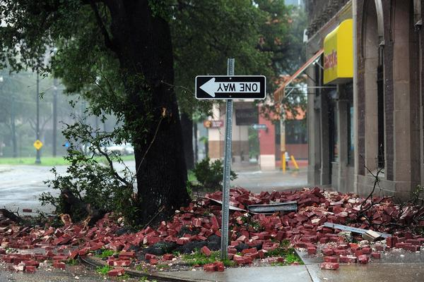 A street sign is turned upside down and bricks cover the sidewalk of a deserted street in New Orleans.