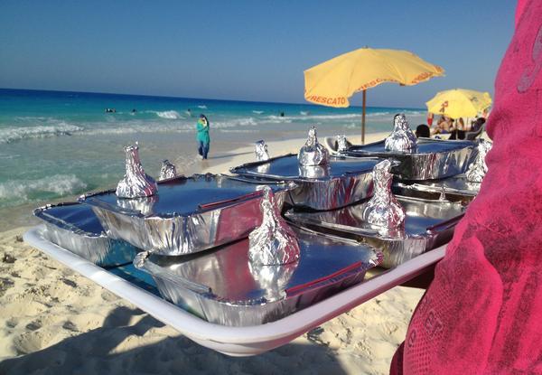 Vendor Amr Abd Elaal balances a tray of gandoufly steamed clams and foil-wrapped half lemons.