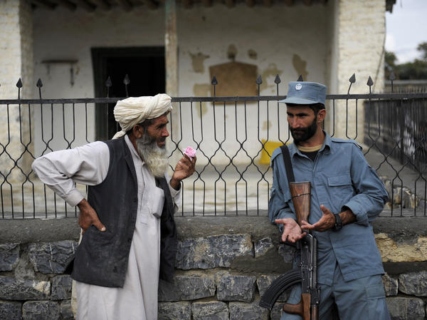 Afghan security forces are already playing a more prominent role, though questions remain about the quality of the forces. Here, an Afghan policeman talks with an elderly man in the eastern province of Khost in August.