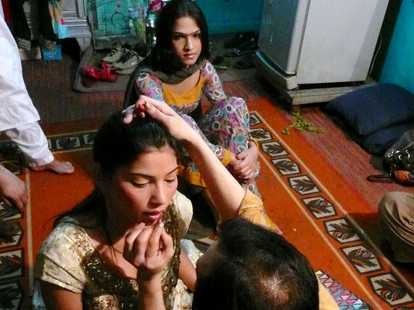 Malaika, 19, sits behind a friend while her makeup is applied at a friend's home in Rawalpindi. The transgender teenager got straight As in school before dropping out because of discrimination from her classmates. Now she dances at weddings and other parties for money.