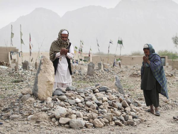 In March, villagers pray over the grave of a victim of a shooting rampage in the Panjwai district of Kandahar province south of Kabul, Afghanistan.