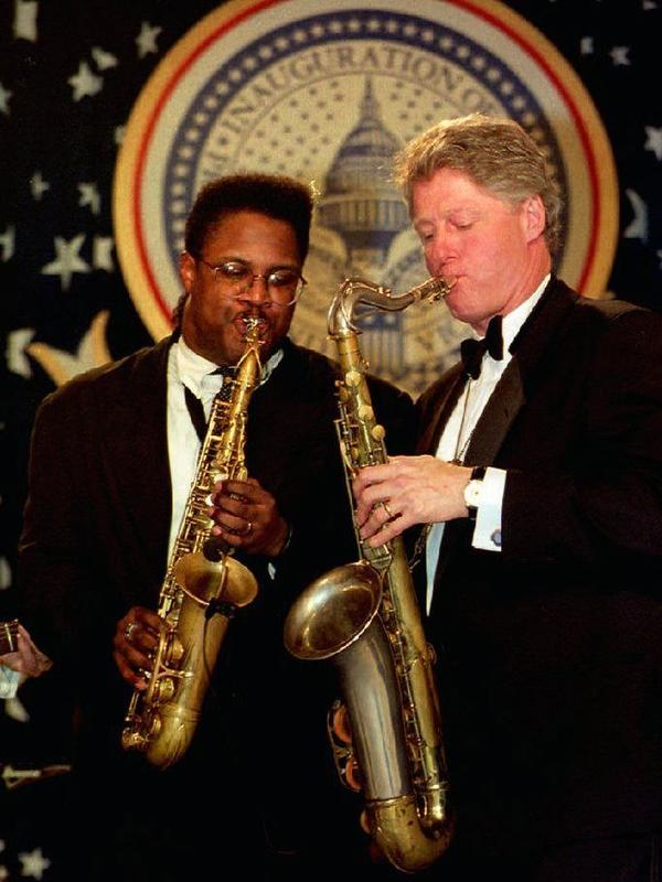 President Bill Clinton plays a saxophone with Everette Harp at the Arkansas inaugural ball on Jan. 20, 1993.