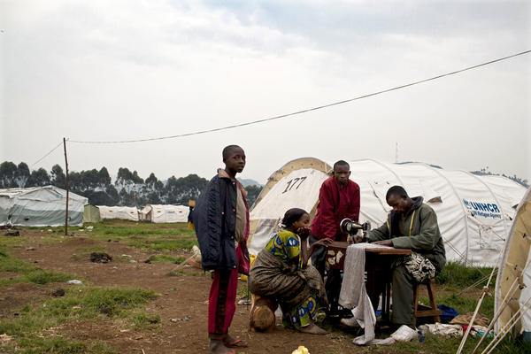 A Congolese man who fled eastern Congo for shelter at a Ugandan refugee camp lugged his sewing machine with him. U.N. officials say tens of thousands have fled  for Uganda and Rwanda in recent months.