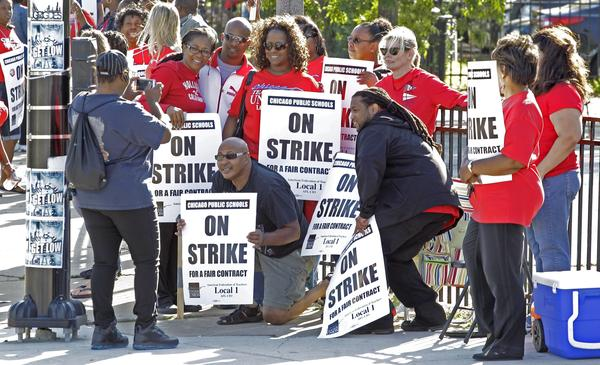 Chicago public school teachers pose for a photo on a picket line as their strike extends into a fifth day.