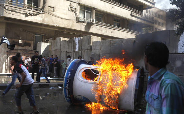 Protesters set a bank security booth on fire during a demonstration near the U.S. embassy in Cairo, Friday.