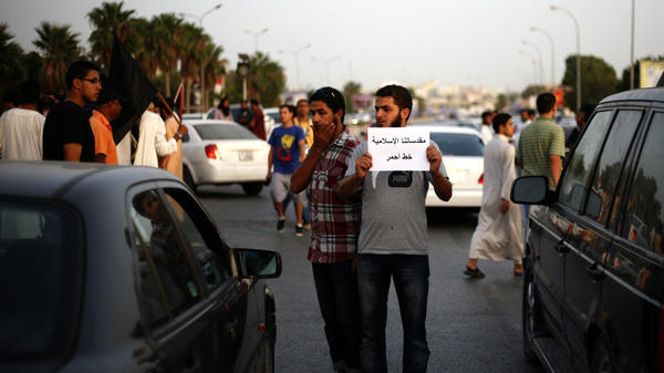 "A Libyan follower of Ansar al-Sharia Brigades carries a placard reads in Arabic ""our Islamic holies are red line,"" during a protest in front of the Tibesti Hotel, in Benghazi, Libya, on Sept. 14, as part of widespread anger across the Muslim world about a film ridiculing Islam's Prophet Muhammad."