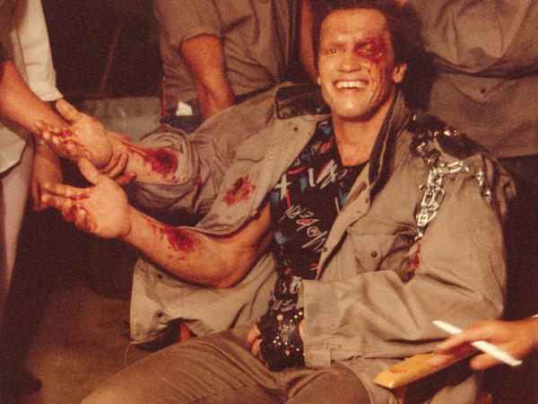 Arnold Schwarzenegger in the makeup trailer for <em>Terminator</em>, getting his do-it-yourself forearm.