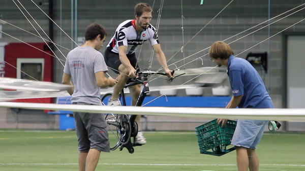 Todd Reichert pedals Atlas into the air, as Cameron Robertson (left) and team member Calvin Moes watch from the ground.
