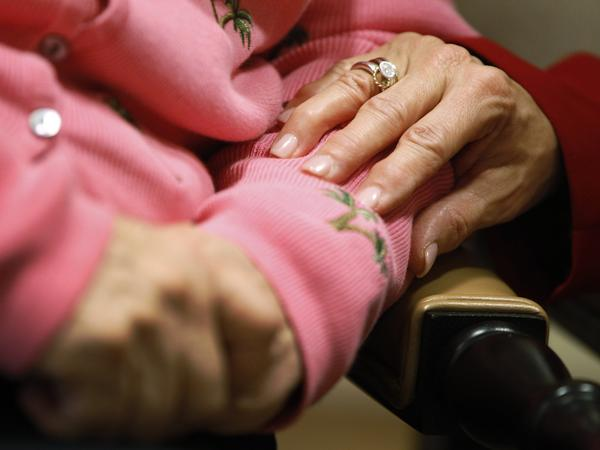 Alexis McKenzie, executive director of the Methodist Home of the District of Columbia Forest Side, an Alzheimer's assisted-living facility, puts her hand on the arm of resident Catherine Peake.