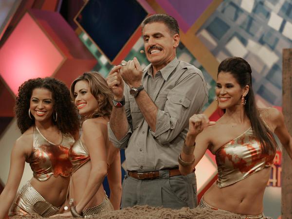 Zoologist Ron Magill points to his wedding ring as dancers surround him during a 2006 taping of <em>S<em>á</em>bado Gigante</em>.