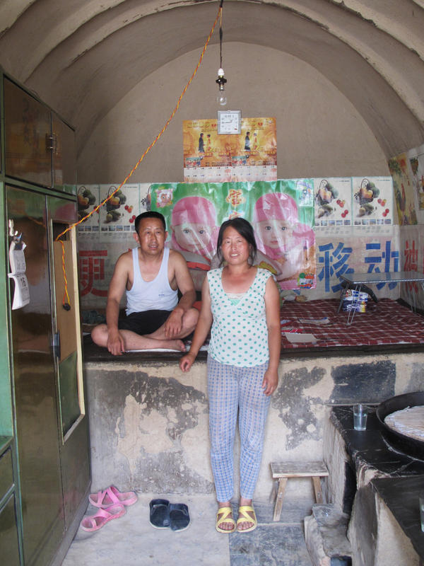 Guo Haiyun, 46, and his wife in their cave home, not far from the revolutionary stronghold of Yan'an. He says he probably only has two or three yuan in cash at home, while he has taken out bank debts he can't return to pay for his daughter's university education.