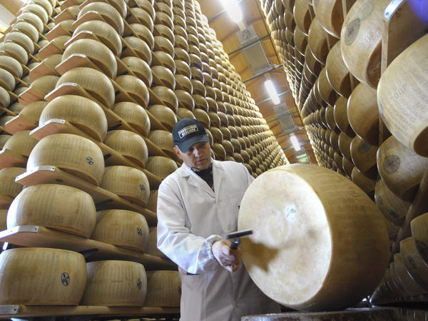 An inspector checks a wheel of Reggiano cheese at the Parmigiano-Reggiano storehouse in Bibbiano, Italy. Earthquakes rocked the region, sending the cheese toppling.