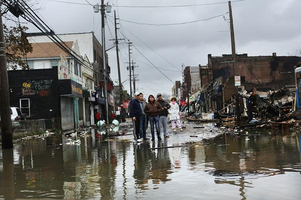 People look at homes and businesses destroyed during Superstorm Sandy on Tuesday in the Rockaway section of Queens, N.Y.