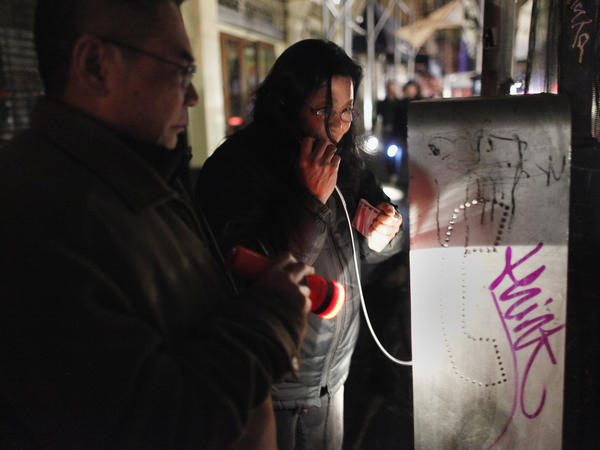 A woman uses a pay phone in the Lower East Village in Manhattan on Wednesday.