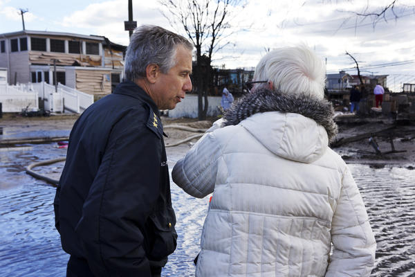 New York Fire Department Chief Joseph Pfeifer consoles a woman who lost her home. The small seaside community lost 111 homes as fires raged in the 50-mph winds of Superstorm Sandy.