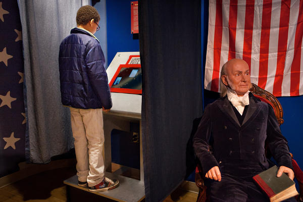 Noah Hope, 10, votes for the next president of the United States during the children's mock presidential election at Madame Tussaud Wax Museum in Washington D.C., as the wax figure of John Quincy Adams looks on.