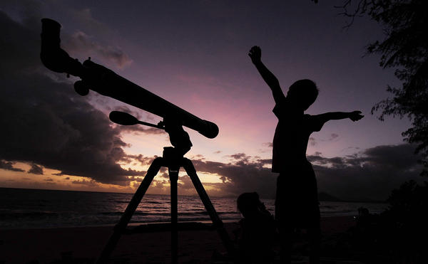 A young boy gets ready to view the solar eclipse with his telescope on Wednesday.
