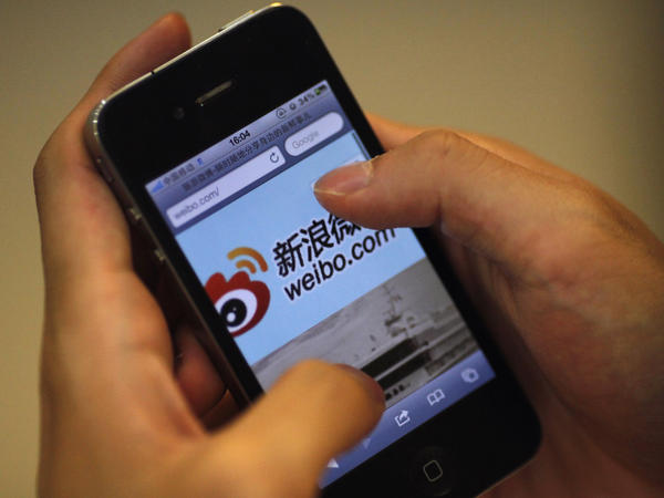 A man holds an iPhone as he visits Sina's Weibo microblogging site in Shanghai earlier this year.