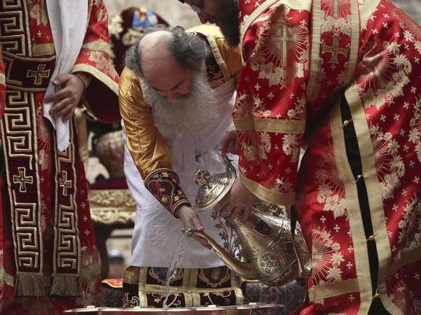 Theofilos III (center) pours water into a basin during the washing of the feet ceremony outside the Church of the Holy Sepulcher in Jerusalem's Old City in April 2011, during Easter celebrations.