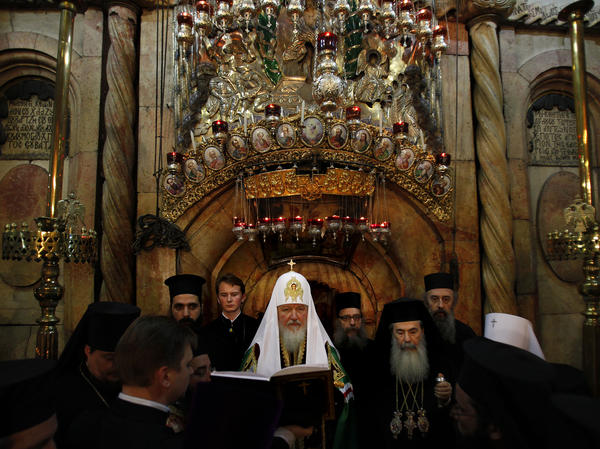Greek Orthodox Patriarch of Jerusalem Theophilos III (right) and Russian Orthodox Patriarch Kirill (center) pray in front of the tomb of Jesus in the Church of the Holy Sepulcher in November.