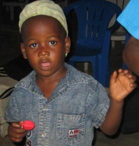 A Nigerian boy receives a dreidel for Hanukkah.