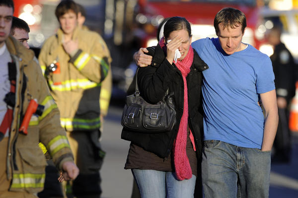 Family members leave a firehouse staging area following the shooting.