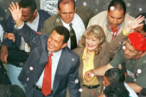 Chavez and his wife, Marisabel, wave to supporters in July 1998, as Chavez arrives at the National Electoral Council to register for the presidential election. He won the election by a landslide.
