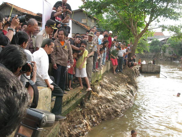 Jakarta Governor Joko Widodo (in white shirt, at left) examines the muddy waters of the Ciliwung River in Jakarta. The city government is planning to dredge the river and relocate residents away from its banks to prevent chronic urban flooding. His talk of providing more services has won him widespread popular support.