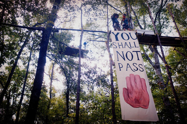 The Tar Sands Blockade protesters hang banners from a 100-foot-long catwalk. There are a total of seven structures suspended in the canopy of the trees with more than 500 feet of wire connecting them.