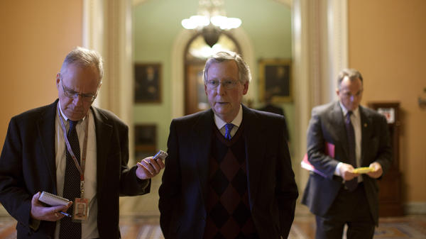 Senate Minority Leader Mitch McConnell walks toward his office after speaking on the Senate floor on Capitol Hill. McConnell and other congressional leaders will meet with President Obama Friday.