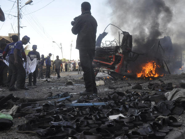 Rescuers carry a sheet to collect body parts near the scene of a bomb explosion in Karachi on Saturday that killed at least six people and . wounded 48. The sandals in the foreground are displayed for sale.
