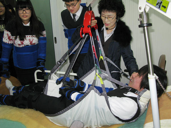 High school student Kim Dong-hyun undergoes a simulated experience as an incapacitated elderly person who is hoisted from his bed into a chair by means of a winch and sling. Training at the Seongnam Senior Complex outside Seoul is intended to help young people understand what the elderly are experiencing.