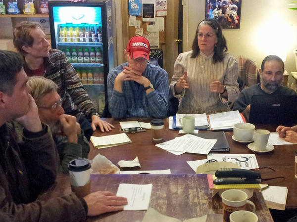 Members of the Saratoga Peace Alliance discuss plans for a street action they plan to stage at the city's upcoming gun show.