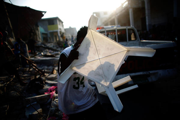 A man carries a stolen plastic table past a police car in Port-au-Prince, Haiti, Jan. 20, 2010.