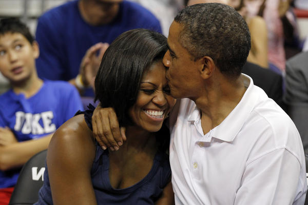 """<strong>Aww:</strong> Obama sneaks an extra smooch after kissing Michelle for the """"Kiss Cam"""" at the basketball game between U.S. and Brazil, on July 16, 2012, in Washington, D.C."""